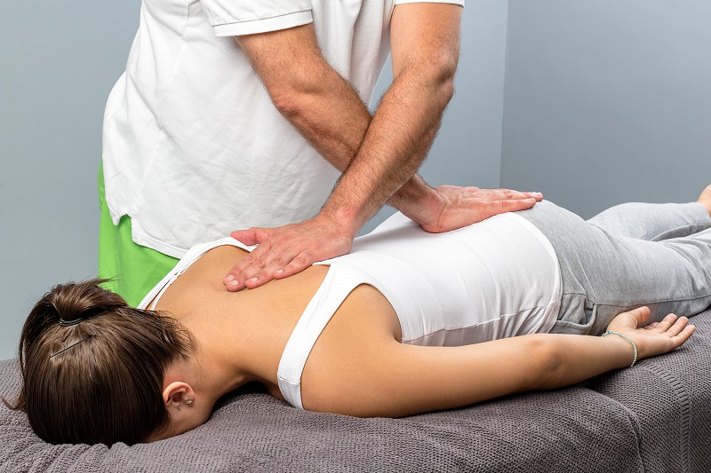 Physiotherapist applying pressure on female spine.